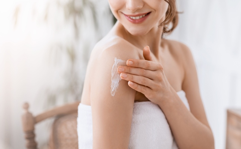 Cropped Image Smiling Woman Applying Cream Shoulder