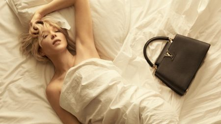 Lea Seydoux poses in bed sheets for Louis Vuitton Capucines 2021 campaign.