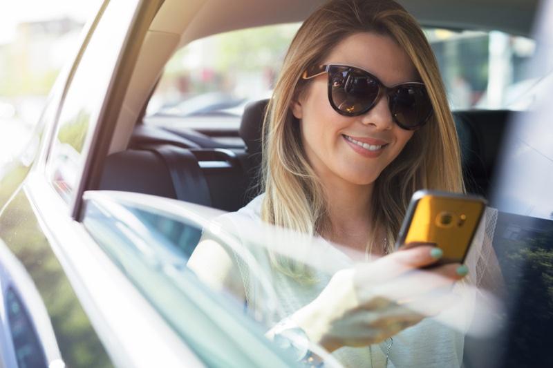 Smiling Woman Holding Phone Car Sunglasses