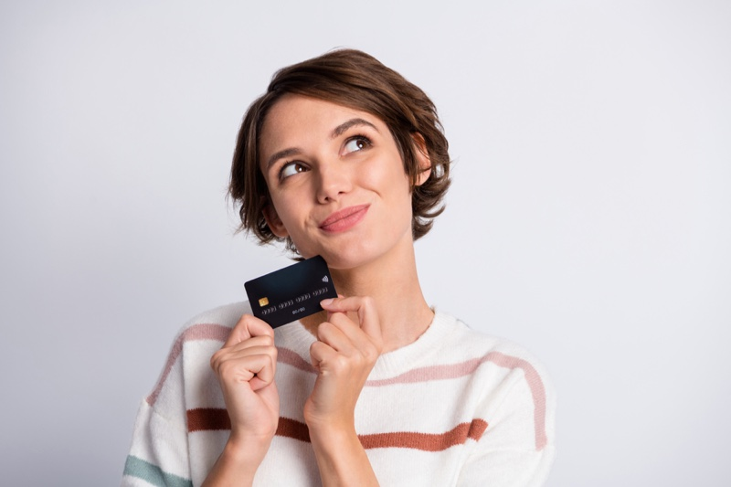 Smiling Woman Thinking Holding Credit Card