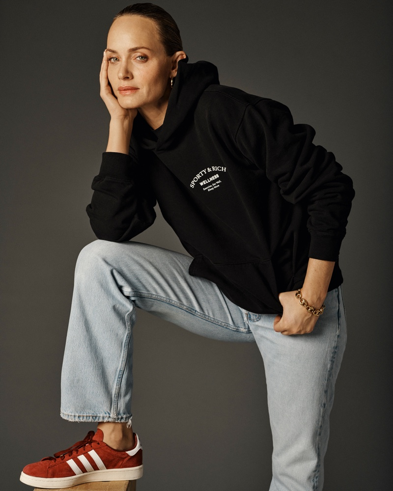 Wearing a hoodie, Amber Valletta poses in Sporty & Rich spring 2021 campaign.