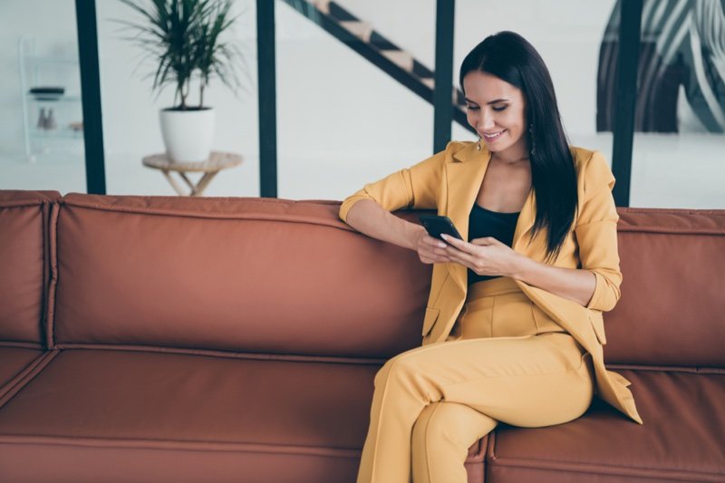 Woman Wearing Yellow Pant Suit Sitting Couch Looking Phone