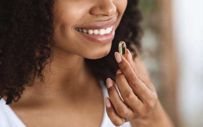 Black Woman Taking Vitamin Smiling Teeth