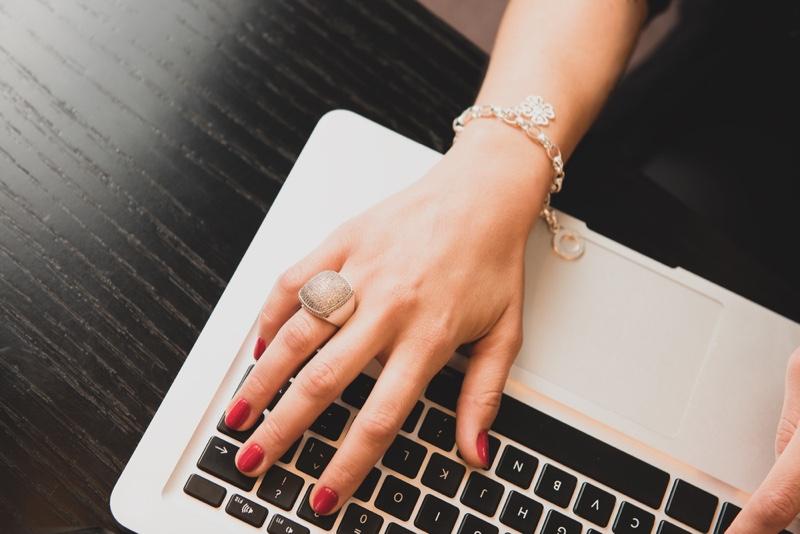 Closeup Woman's Hand Ring Bracelet Using Laptop