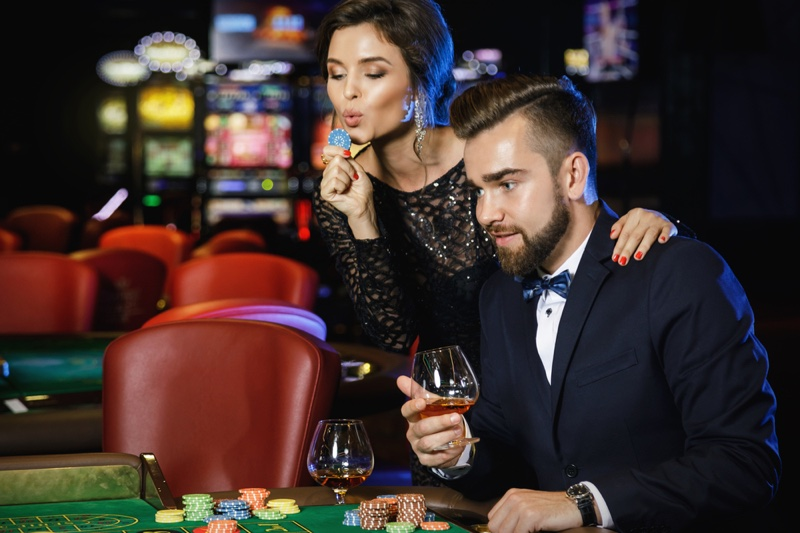 Couple Casino Woman Blowing Poker Chip