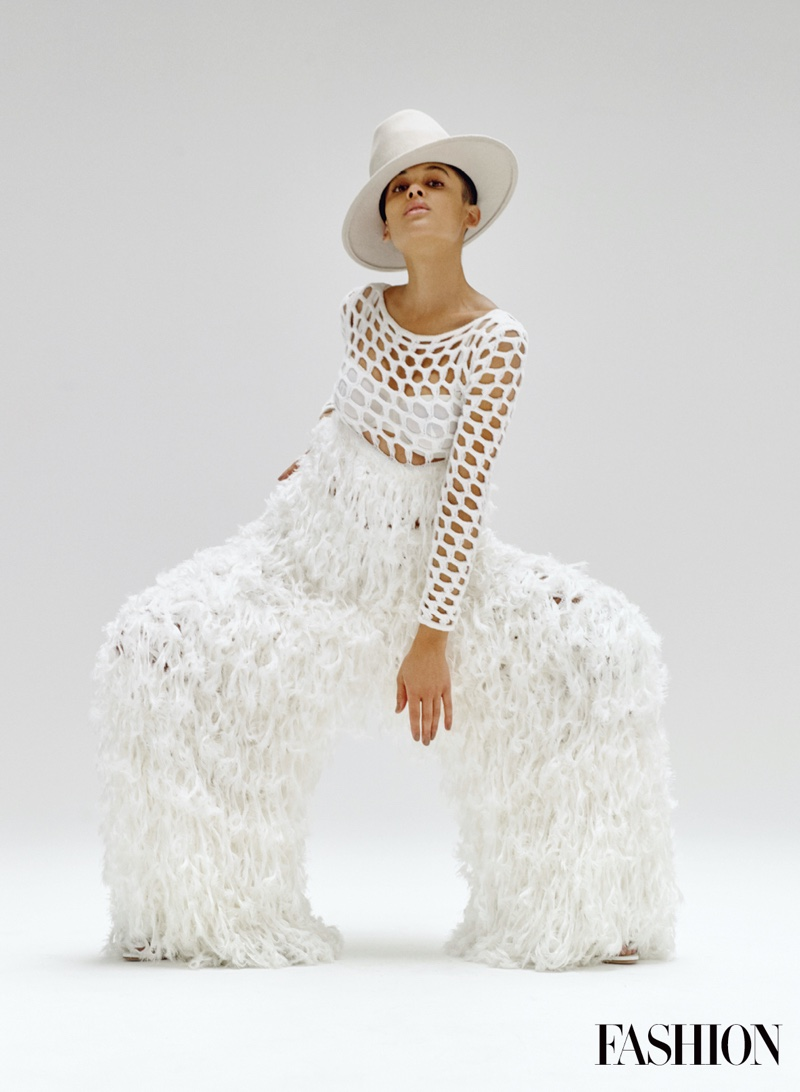 Dressed in white, Jordan Alexander poses in JW Anderson jumpsuit with Alexandre Birman shoes and Esenshel hat.