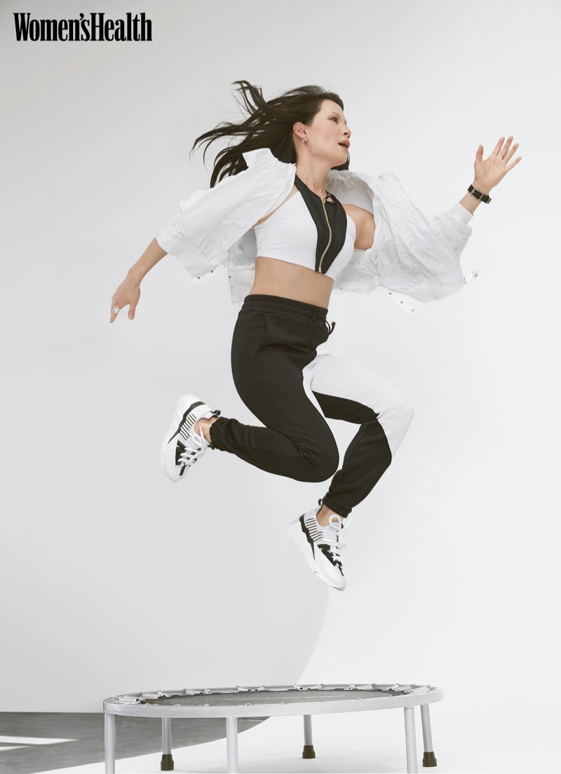 Lucy Liu takes a leap in Athleta jacket, Oye Swimwear top, Koral pants, and Pierre Hardy sneakers.