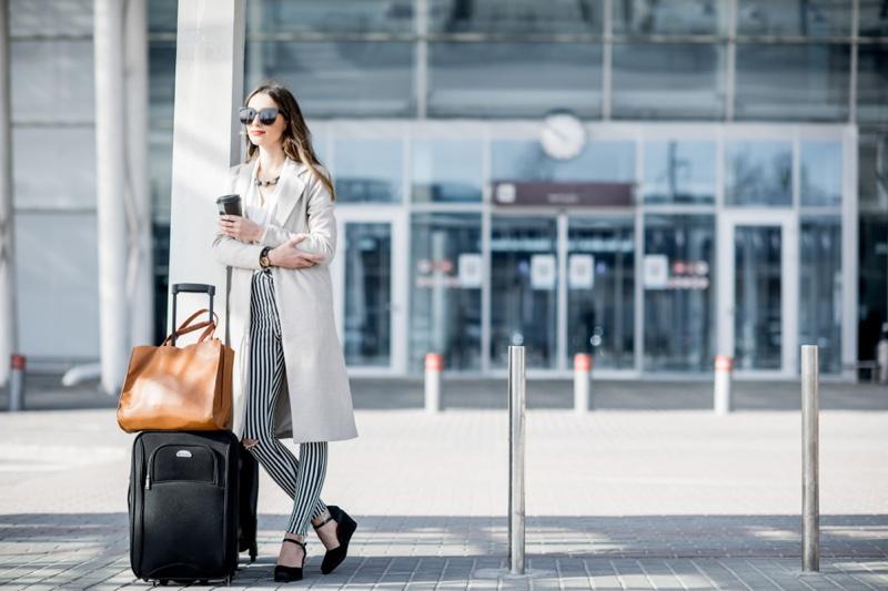 Fashionable Woman Traveling Luggage Bag Coat Striped Pants
