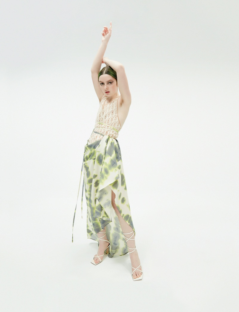 Striking a pose, Lachlan Watson wears a top and printed skirt.