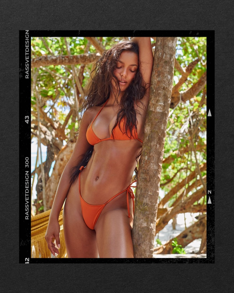 Lais Ribeiro wears Tropic of C Praia top and bottom in burnt orange.