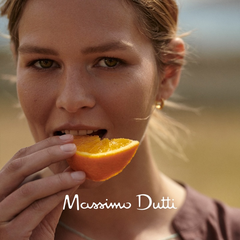 Anna Ewers eats an orange in Massimo Dutti style guide.