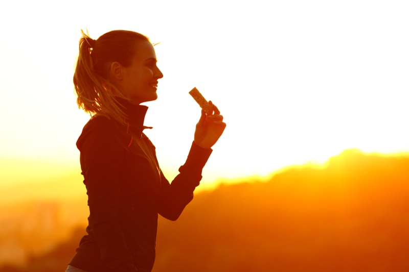 Smiling Woman Holding Protein Bar Outdoors Sun