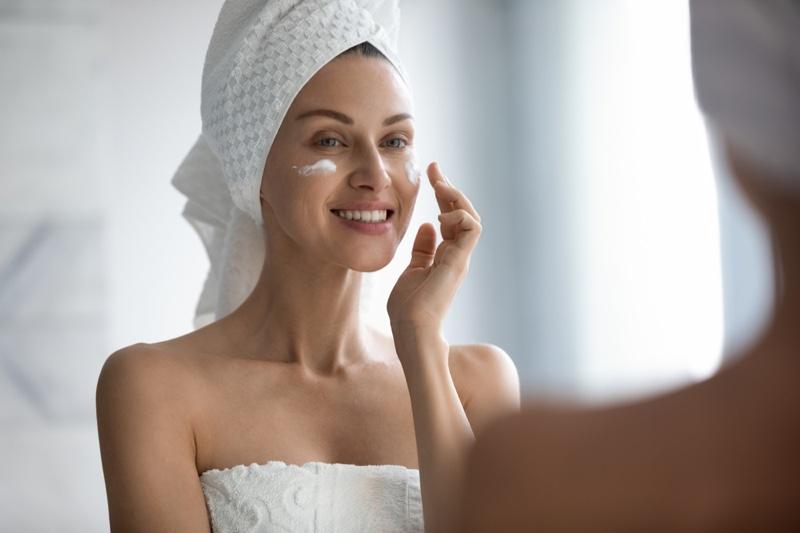 Woman Applying Face Cream Mirror Skincare Towel Cover Hair