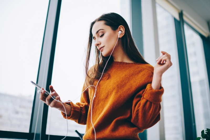 Woman Listening Music Podcast Earphones Orange Sweater
