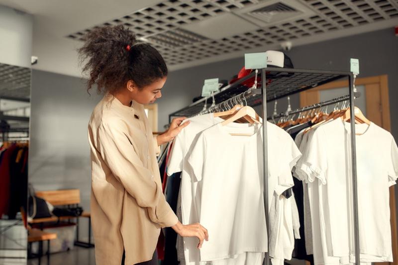 Woman Selecting T-Shirts Hanging Rack