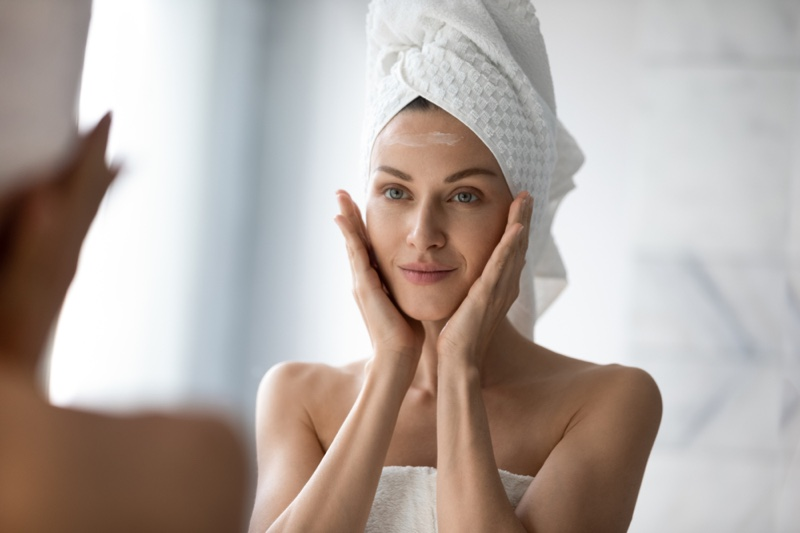 Woman Skincare Touching Face Towel Covering Hair