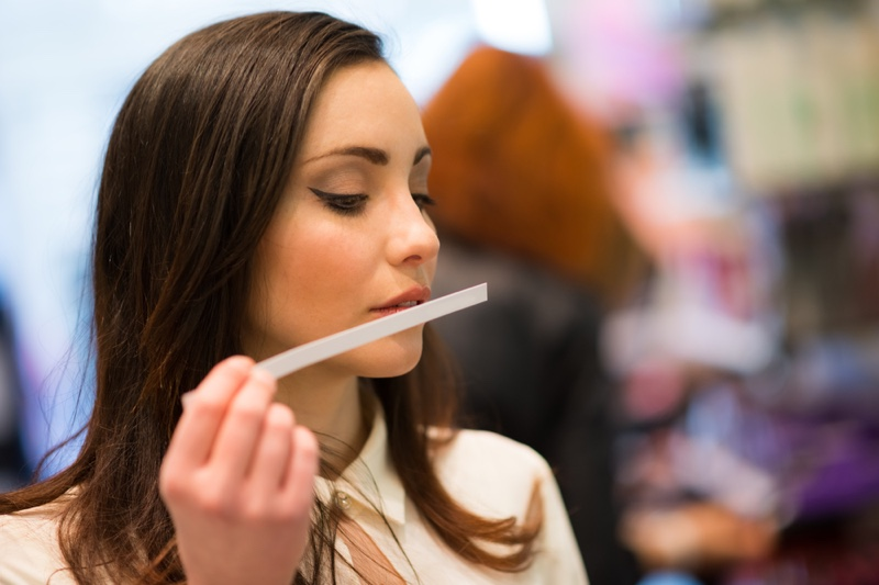 Woman Smelling Perfume Testing Strip
