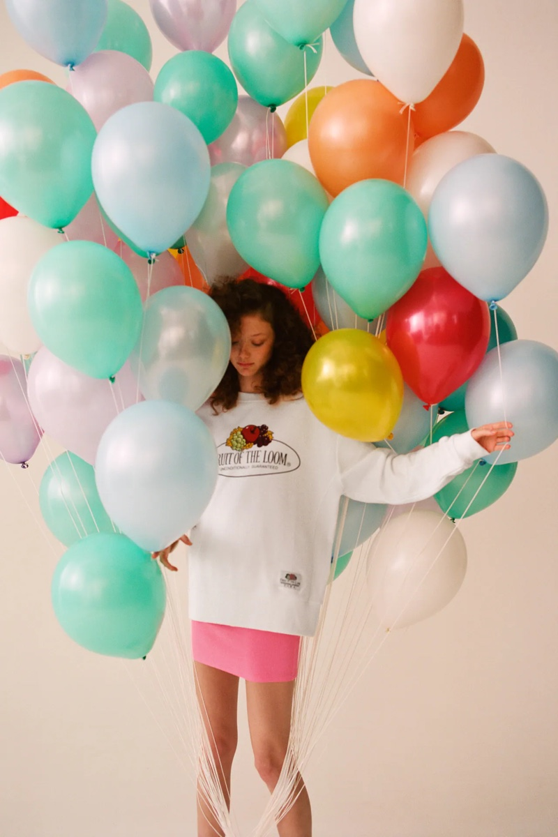 Posing with balloons, Sara Grace Wallerstedt models Zara x Fruit of the Loom collaboration.