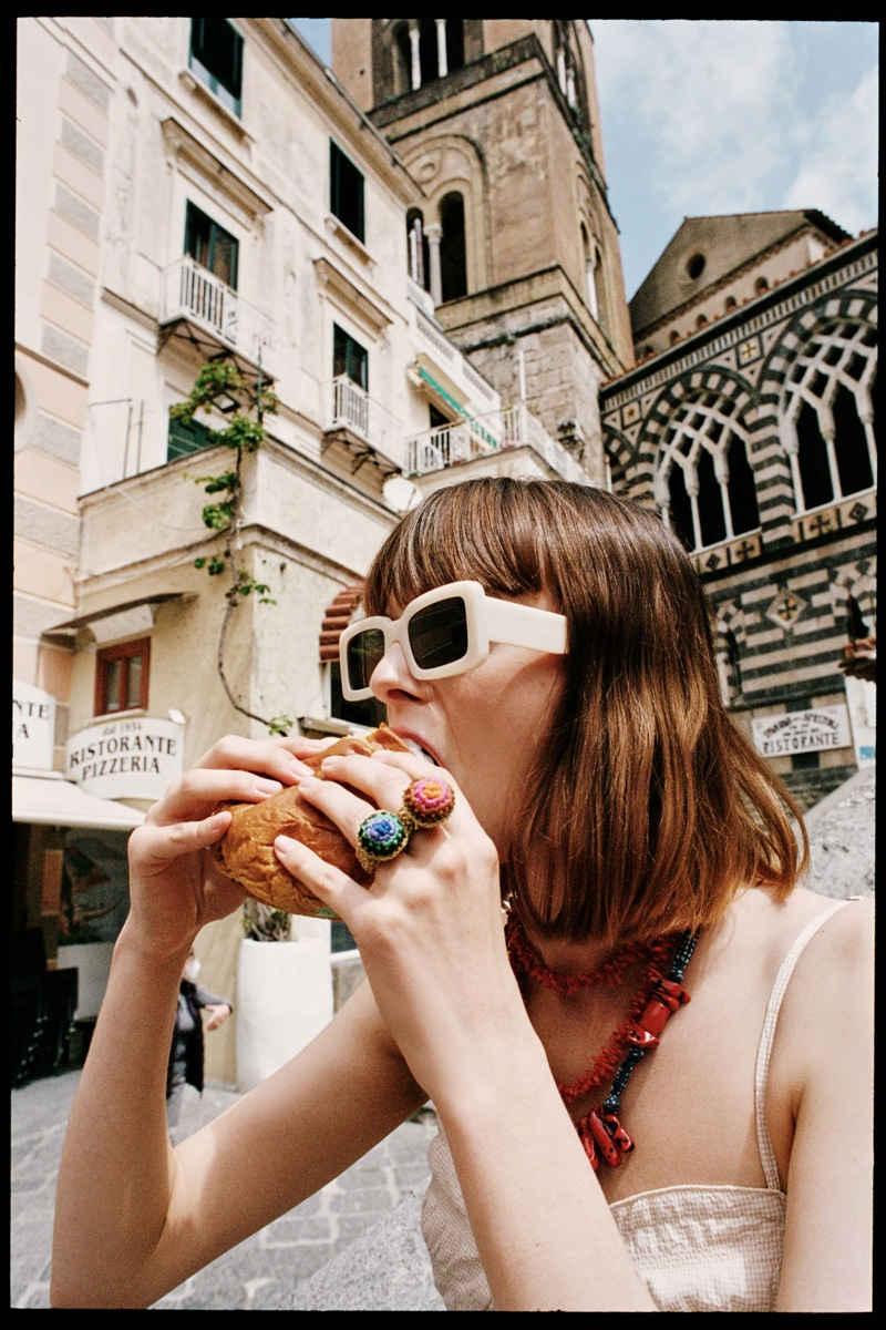 The model eats a hamburger with Zara's stylish sunglasses.