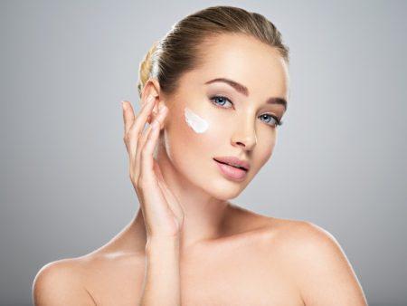 Beauty Model Applying Face Cream