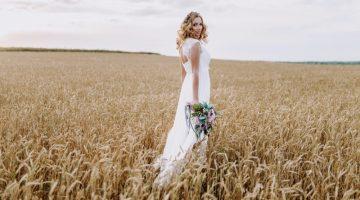 Bride Outdoors Long Wedding Dress Holding Flowers Wheat Field