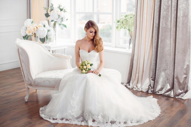 Bride Sitting Long Wedding Dress Strapless Holding Flowers