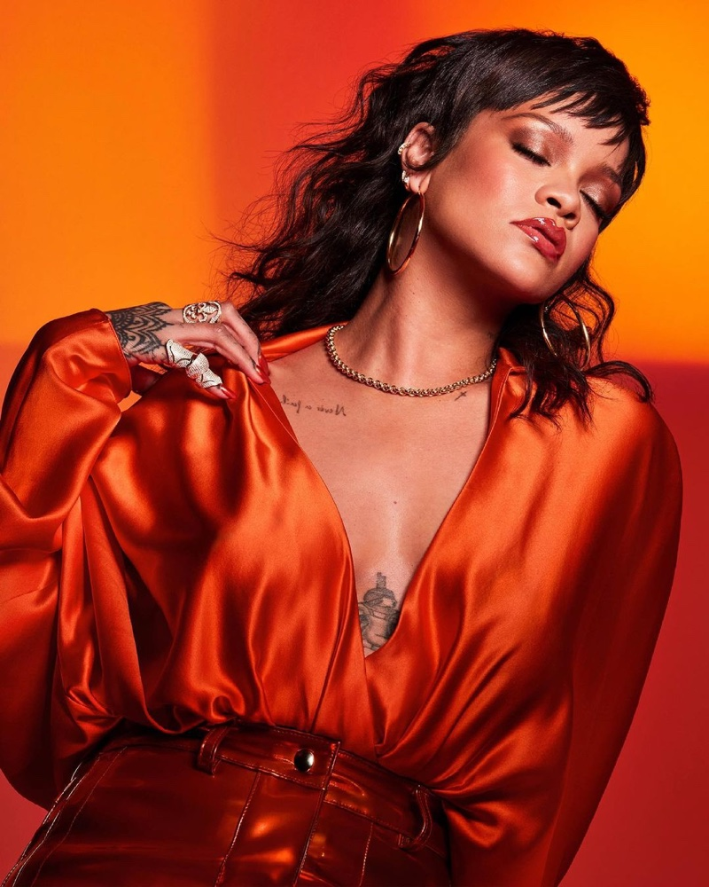 Showing off her tattoos, Rihanna fronts Fenty Beauty Gloss Bomb Heat campaign.