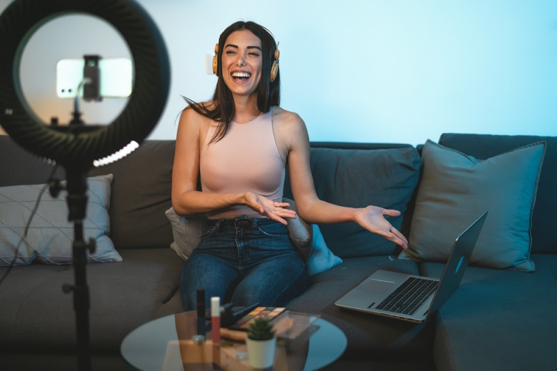 Smiling Woman Recording Video vlogger Couch