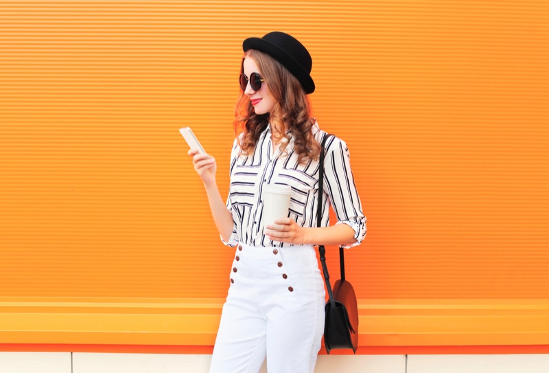 Woman Striped Blouse White Pants Holding Phone Cup