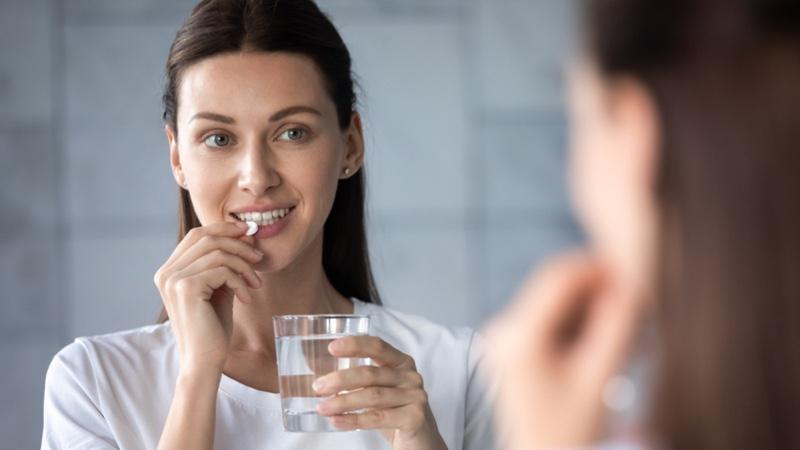 Woman Taking Vitamin Glass Water