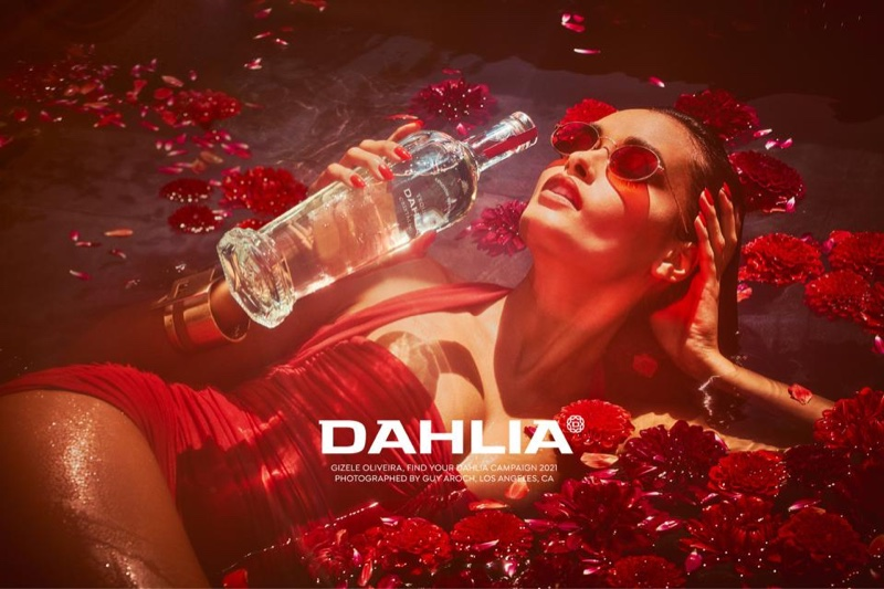 Wearing a red swimsuit, Gizele Oliveira poses for Dahlia Tequila campaign.