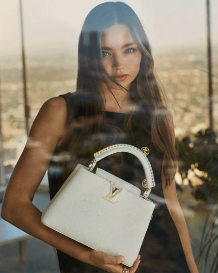 Posing by a window, Miranda Kerr fronts Louis Vuitton Capucines 2021 campaign.