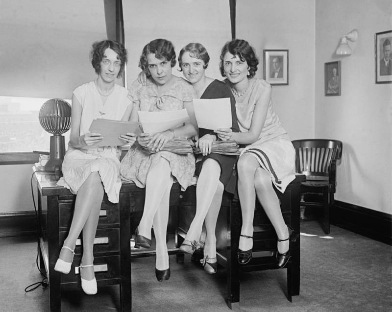 Young women working at an office wear knee-length dresses and different shoe styles during 1929.