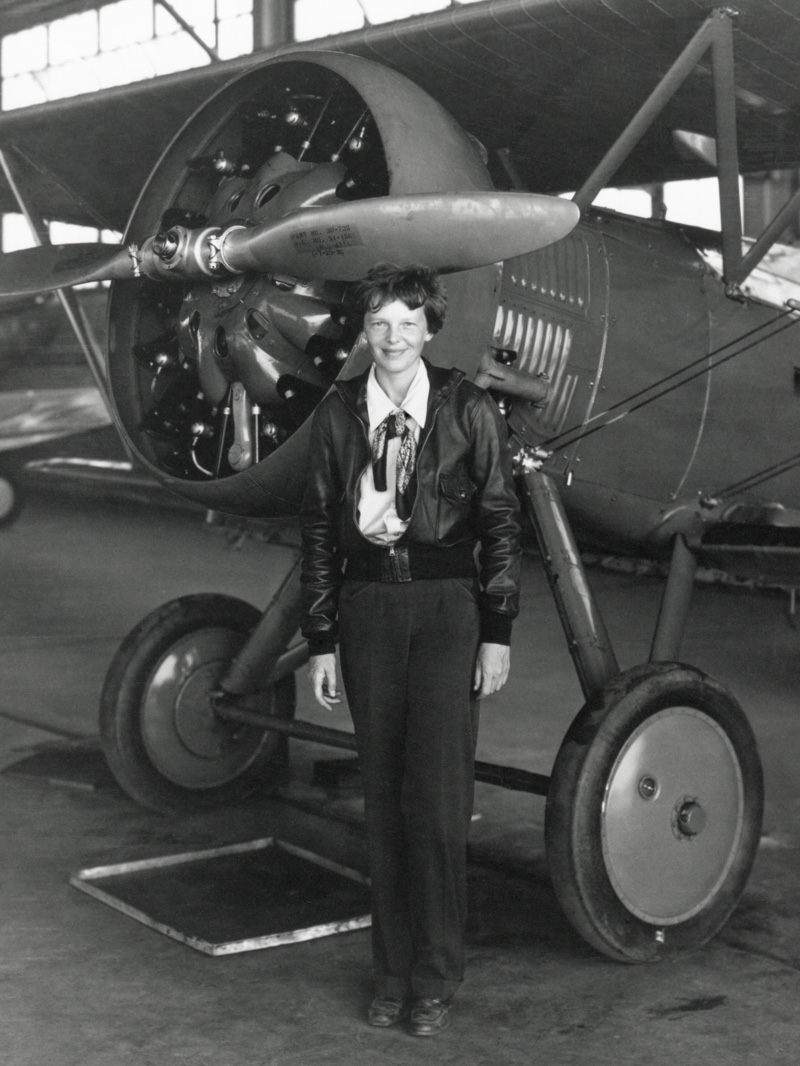 Aviator Amelia Earhart wears pants in a 1936 photo while posing next to an airplane. Photo: Shutterstock.com