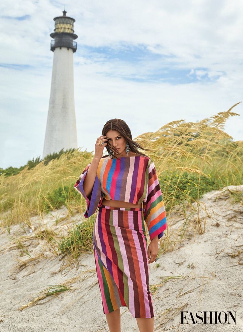 Wearing colorful stripes, Ashley Callingbull poses in 4Kinship top and skirt.