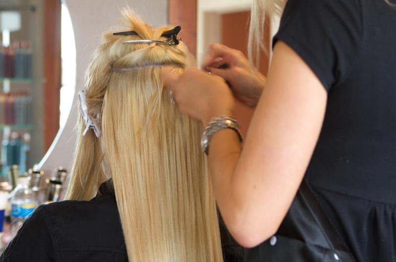 Hairstylist Applying Extensions Blonde Hair