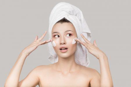 Model Applying Moisturizer Face Skincare Towel
