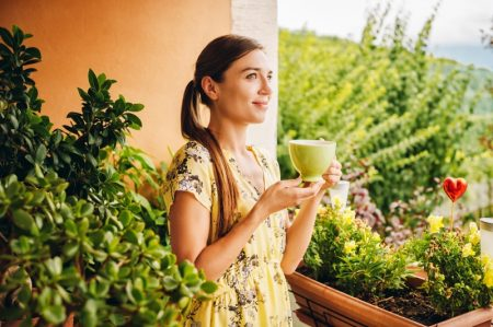 Young Woman Holding Green Tea Cup Yellow Dress Plants
