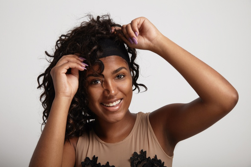 Black Woman Putting On Curly Wig