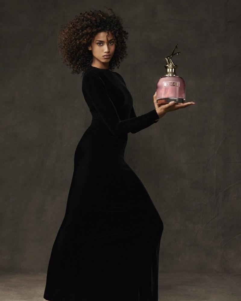 Model Imaan Hammam poses with Jean Paul Gaultier Scandal fragrance bottle.