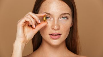 Model Freckled Face Holding Vitamin Gel