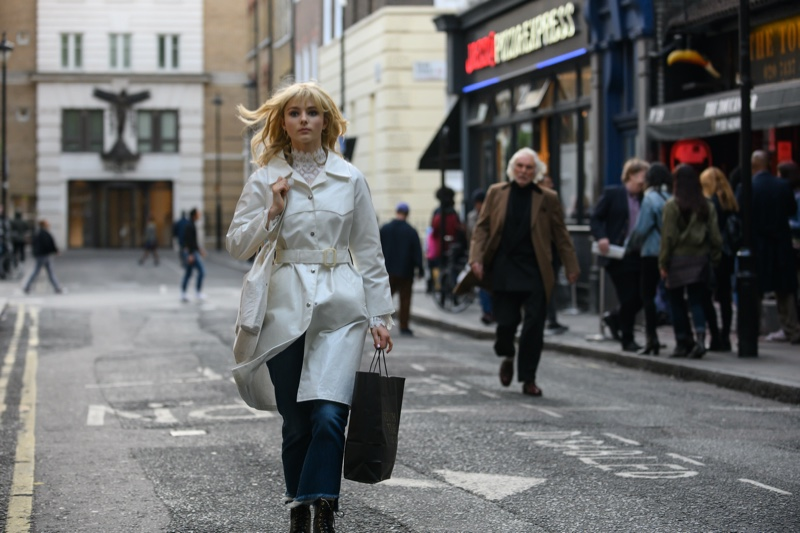 Thomasin McKenzie as Eloise wears a stylish white coat in LAST NIGHT IN SOHO. | Photo Credit: Parisa Taghizadeh / © 2021 Focus Features, LLC