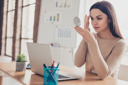 Woman Looking at Makeup in Mirror