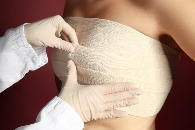 Doctor Bandaging Woman's Breasts