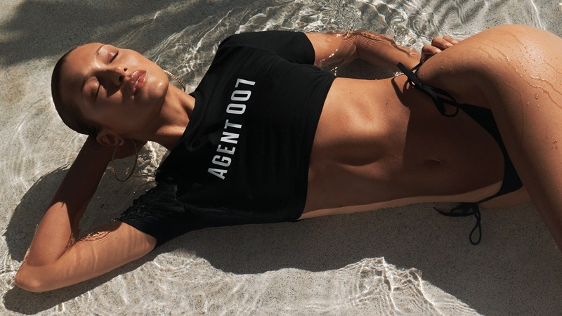 Bella Hadid wears cropped shirt for Michael Michael Kors x 007 collaboration campaign.