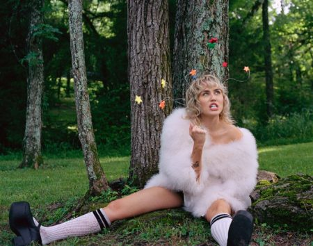 Posing underneath a tree, Miley Cyrus models Gucci coat, socks, and shoes. Photo: Brianna Capozzi/Interview, Courtesy Columbia Records
