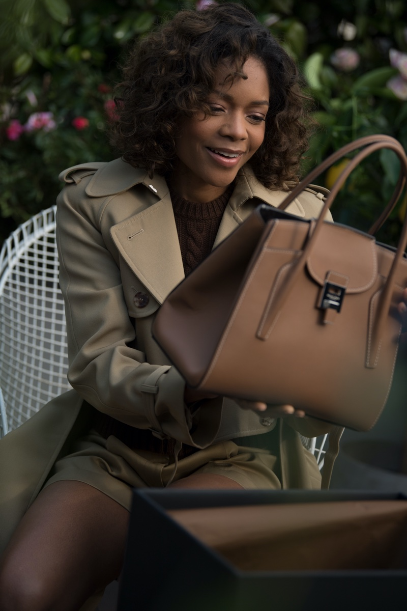 No Time to Die actress Naomie Harris poses with Michael Kors Collection x 007 Bond Bancroft satchel bag.