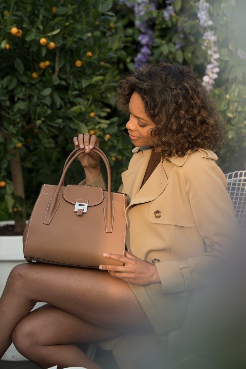 Actress Naomie Harris poses with design from Michael Kors Collection x 007 collaboration