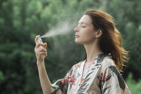 Woman Applying Face Mist Skin