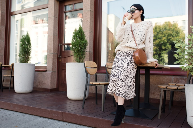 Woman White Sweater Print Skirt Outfit Drinking Coffee